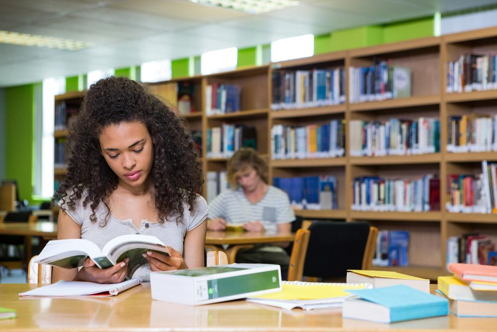 aluna estudando em biblioteca